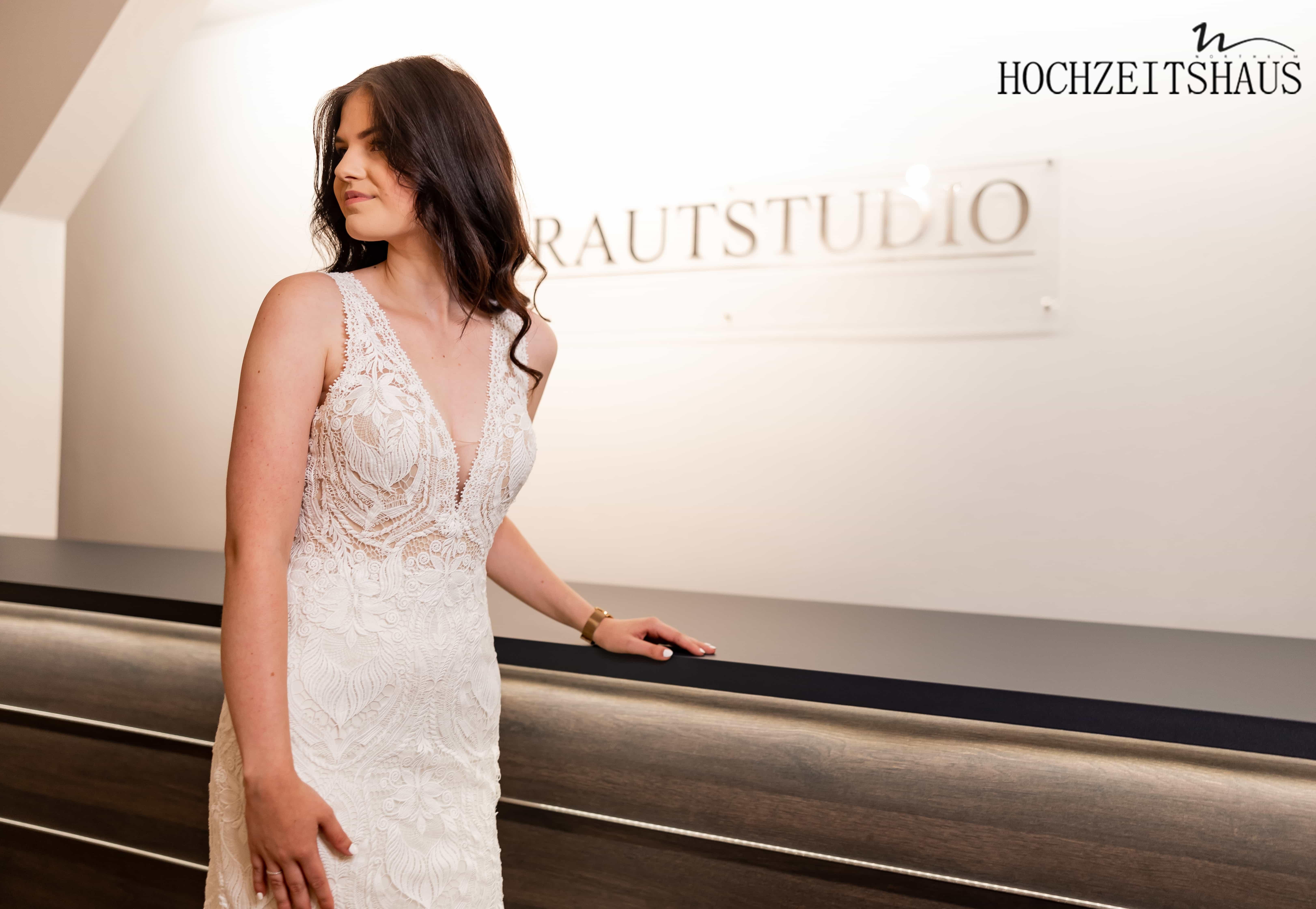 junge Braut vor Spiegel lachend in Brautkleid