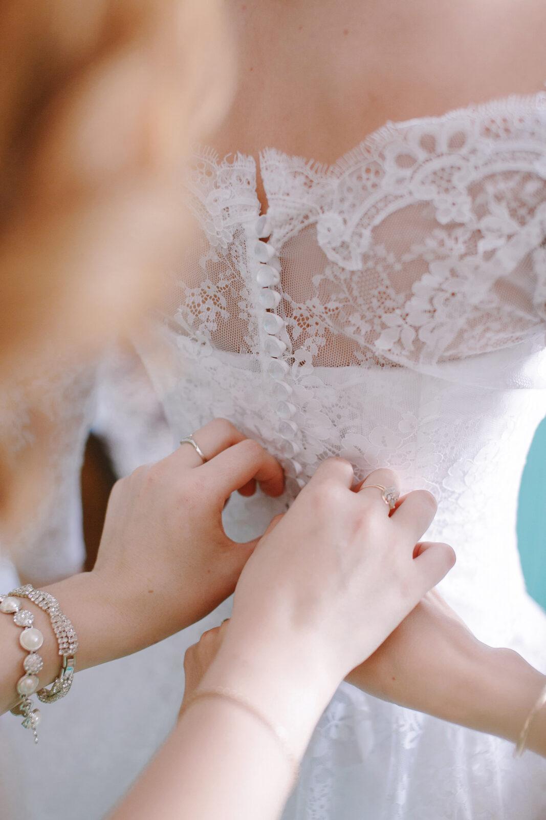 Zuknöpfen des Brautkleides von Frau mit Ringen
